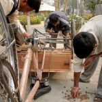 Hier wird ein gespendetes Dreirad von Mitarbeitern zusammengebaut, damit es für den Straßenverkauf genutzt werden kann.