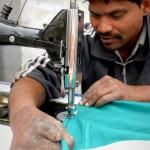 Ein Patient wurde zum Mitarbeiter und arbeitet mit viel Geschick an der Nähmaschine, obwohl er einen Teil seiner Finger durch eine Hautkrankheit verloren hat.
